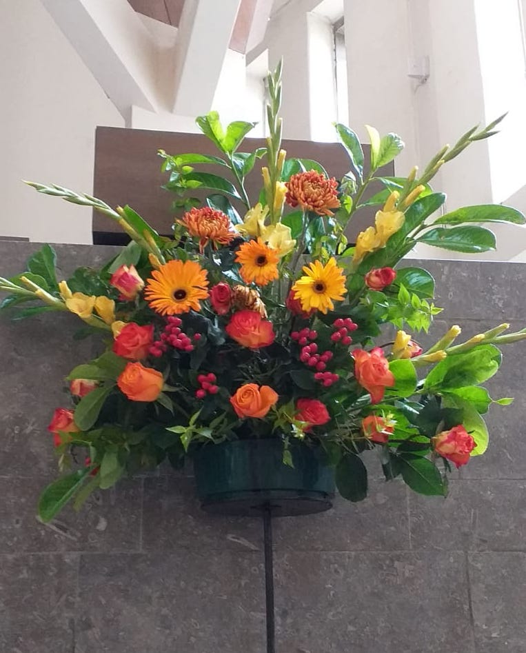 An arrangement of orange and yellow flowers displayed in front of the pulpit.