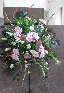 an arrangement of pink and white flowers in front of the pulpit
